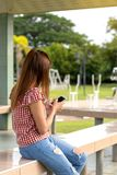 Female side view playing mobile in the garden. stock photography