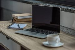 Close up view of opened laptop with blank screen, cup of coffee and notebook. On table Royalty Free Stock Image
