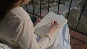 Young girl illustrator drawing portrait on balcony
