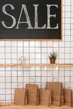 Paper shopping bags and sale sign in boutique Stock Images