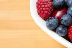 Close up view of par of plate full of berries on table Stock Photo