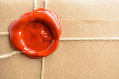 Close up view of parcel wrapped in craft paper with rope and red. Sealing wax, macro photo stock image