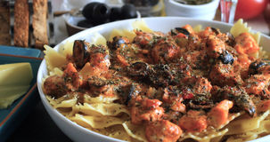 Close up view of pasta with fresh salmon and black olives Stock Photography