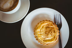 Close up view of a pastry beside a cappuccino Royalty Free Stock Images