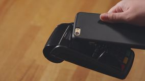 Close up view of payment terminal and smartphone. stock video