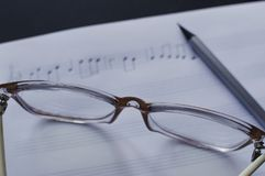 Music notes writing composer creating musician art. Close-up view of the pencil, eyeglasses laying on the sheet notes with handwritten notes. The concept of the royalty free stock photo