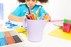Close-up view of pencils and African girl writing Stock Image