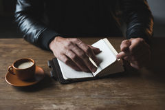 Close-up view of person sitting at wooden table with diary Stock Image