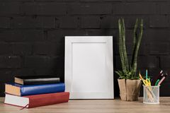 Close up view of photo frame, office supplies, plant in flowerpot and books. On wooden tabletop stock images