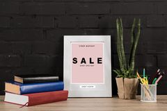 Photo frame and book on tabletop. Close up view of photo frame, office supplies, plant in flowerpot and books on wooden tabletop stock photos