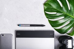 Close-up view of photographer`s of graphic designer`s workplace. Tablet, stylus, camera, smartphone, monstera green leaf royalty free stock image