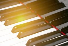 Close up view of piano keyboard with sun flare. stock photography