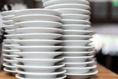 Pile of white plates in restaurant, close up stock photos
