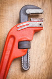 Close up view on pipe wrench on wooden board Royalty Free Stock Images