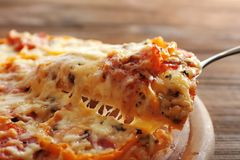 Close up view of pizza slice lifted. From wooden plate royalty free stock photography