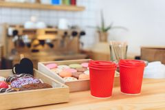 Close-up view of plastic cups and tasty cookies on wooden counter. In cafe stock image