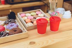 Close-up view of plastic cups and various pastries on wooden counter. In cafe stock photography