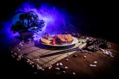 Close up view of plate with japanese food inside. Japan traditional food on wooden table with decoration of bonsai tree and moon. On toned foggy background stock images