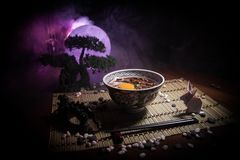 Close up view of plate with japanese food inside. Japan traditional food on wooden table with decoration of bonsai tree and moon. On toned foggy background royalty free stock image