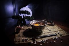 Close up view of plate with japanese food inside. Japan traditional food on wooden table with decoration of bonsai tree and moon. On toned foggy background stock image
