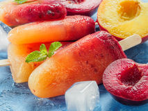 Close up view of plum and peach popsicle on blue background. Close up view of plum and peach popsicle on blue concrete background. Fruit popsicles ice cream with Stock Images