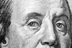 Close up view Portrait of Benjamin Franklin on the one hundred dollar bill. Background of the money. 100 dollar bill with Benjamin. Franklin eyes macro shot royalty free stock image