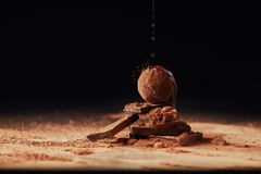 Close up view of pouring caramel onto heap made of truffle and chocolate bars. On black royalty free stock images