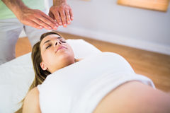 Close up view of pregnant woman getting reiki treatment Royalty Free Stock Images