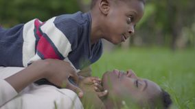 Close-up view of pretty African American woman lying on the grass in the park, her little son lying on top of her and. Kissing woman. Mother and a boy resting stock footage