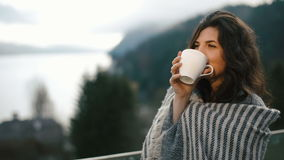 Close-up view of the pretty woman wrapped in the plaid is drinking the coffee and enjoying the timespending in the. Mountains stock video footage