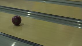 Close-up view of the purple bowling ball orlling along the alley at the high speed. stock footage