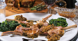 Close up view of a rack of lamb with mint sauce and spinach Royalty Free Stock Photos