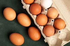 Close-up view of raw chicken eggs in grey box, egg white, brown egg on green background. stock photos