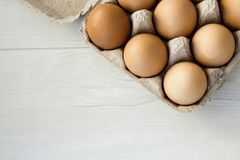Close-up view of raw chicken eggs in egg box on white wooden background. stock photo