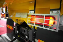 Close up view on rear car tipper truck red and yellow light with silver metal protective cover housing. Commercial transport indus stock photo
