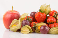 Close up view of red apple with orange physalis, purple grapes and red strawberries. Royalty Free Stock Photography