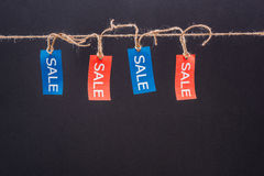 Close-up view of red and blue sale tags hanging on rope isolated on black Stock Photography