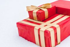 Close-up view of red gift boxes with golden ribbons. In snow stock image