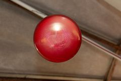 A Red Heating Light. A close up view of a red light that is hanging over a kennel to keep animals warm in the cold winter royalty free stock image