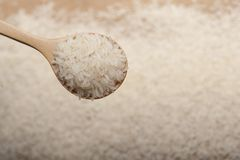 Close up view of rice in a wooden spoon  on wooden background stock photo