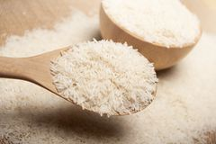 Close up view of rice in a wooden spoon and bowl on wooden background royalty free stock photo