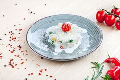 Close up view on risotto with cherry tomato, herps and spices on wooden background. stock photography