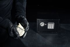 Close-up view of robber in gloves taking dollars royalty free stock image