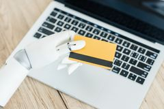 Close-up view of robot holding credit card above laptop. On wooden table royalty free stock photo