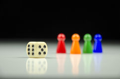 Close-up view of a row of colorful figures at the back with a playing cube on a blurred white-black background. With reflection stock image