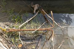 A Rusted Anchor. A close up view of a rusted old anchor on the edge of a river bank stock image