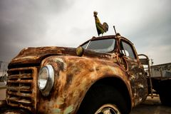 Rusty old pickup  / Vintage rusty car. Close up view of Rusty old pickup with rooster on top Stock Photo