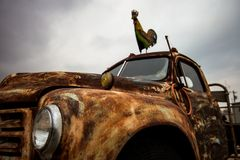 Rusty old pickup truck / Vintage rusty car. Close up view of Rusty old pickup truck with metal rooster on top Stock Photo