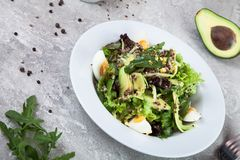 Close up view on salad with quinoa, avocado and egg on a concrete background. stock images