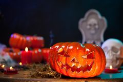 Close up view of scary orange pumkin on a wooden table for halloween celebration. Creepy human skull royalty free stock image